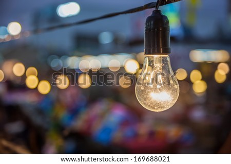 Tungsten lamp with a bokeh background design - stock photo