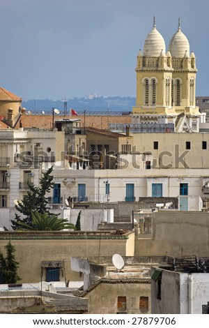 Tunisia. Tunis - old town (medina) seen from roof top. There is steeples of Tunis Cathedral (St Vincent de Paul) on second plan - stock photo