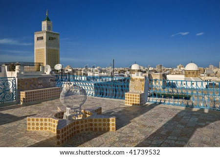 Tunisia. Tunis - old town (medina). Terrace of Palais d'Orient with ornamental wall covered tiles. There is minaret Zitouna Mosque on left side - stock photo