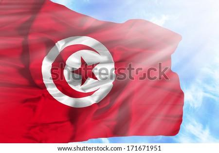 Tunisia waving flag against blue sky with sunrays - stock photo