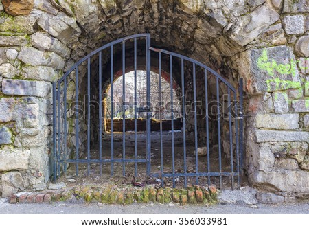 Tunnel entry locked with metal gates - stock photo