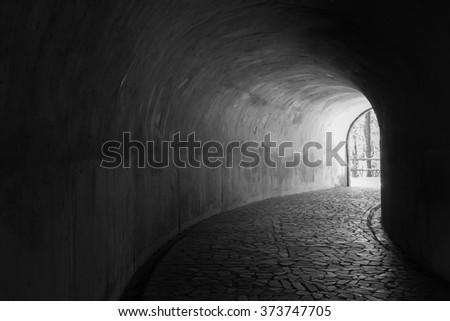 Tunnel in the mountain with a granite footpath