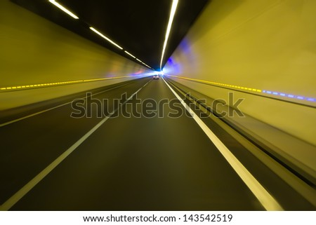 Tunnel of a motorway in the Alps, dynamic motion blurred image - stock photo