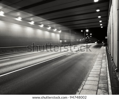 Tunnel road area at night with a smooth car lights trace. - stock photo