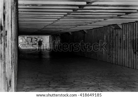 Tunnel underground pedestrian crossing with a picture of graffiti on the walls. Ideal for creative design scene. Selective focus. Black and white stylized photo film - stock photo