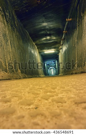Tunnel with a light at the end a exit sign - stock photo