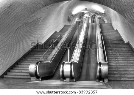Tunnel with a long row moving stairways leading deep down to the underground subway trains of Lisboa Portugal - stock photo