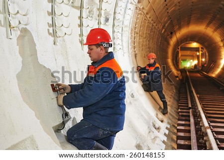 Tunneller worker installing fixture in underground subway metro construction site - stock photo