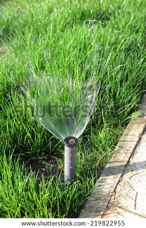Turbo-driven pop-up sprinkler watering the fresh green lawn grass in the summer garden - stock photo
