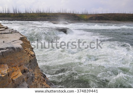 Turbulent rapids on the river. A powerful rapid on the Taimyr Peninsula in the Krasnoyarsk region of Russia.