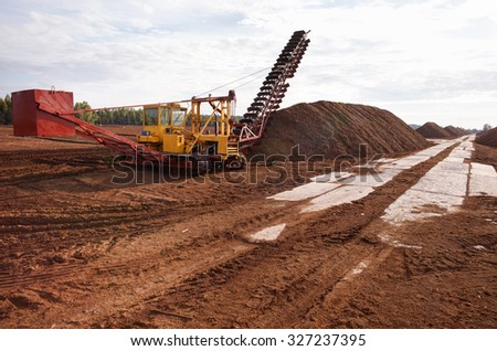 Turf extraction field with excavator tractor - stock photo