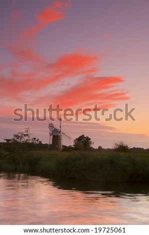 Turf Fen Windmill on the Norfolk Broads against a red evening sky.