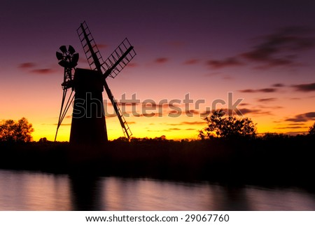 Turf Fen Windmill on the Norfolk Broads against a red evening sky. - stock photo