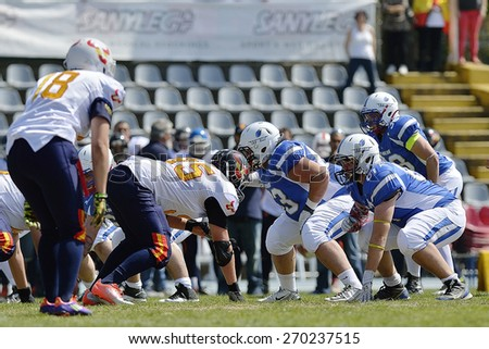 TURIN, ITALY - APRIL 12, 2015: Unknown american football players fight during match. Italian U19 team win the qualifying match with Spain for European championship, in the Nebiolo Stadium in Turin. - stock photo