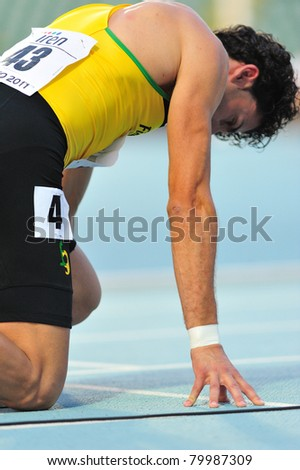 TURIN, ITALY - JUNE 26: Andrea Barberi positions himself at the start of the 400m men sprint race during the 2011 Summer Track and Field Italian Championship meeting on June 26, 2011 in Turin, Italy. - stock photo
