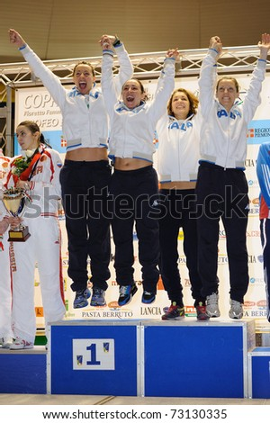 TURIN, ITALY - MARCH 13: Italy team (Di Francisca, Vezzali, Arrigo,  Salvatori) stands at first place podium of team tournament of the 2011 Women world fencing cup on March 13, 2011 in Turin, Italy - stock photo