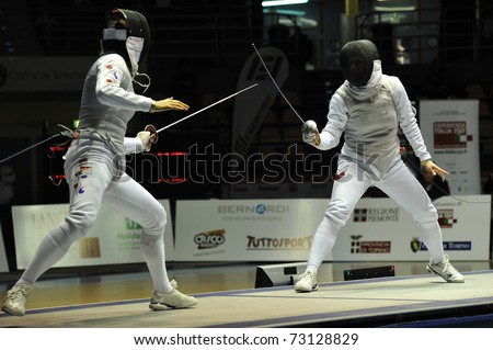 TURIN, ITALY - MARCH 13: JEON Hee Sook (KOR) fight against SYNORADZKA Martyna (POL) during team tournament semifinal match of the 2011 Women world fencing cup on March 13, 2011 in Turin, Italy - stock photo