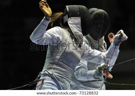 TURIN, ITALY - MARCH 13: NAM Hyun Hee (KOR) fight against SYNORADZKA Martyna (POL) during team tournament semifinal match of the 2011 Women world fencing cup on March 13, 2011 in Turin, Italy - stock photo