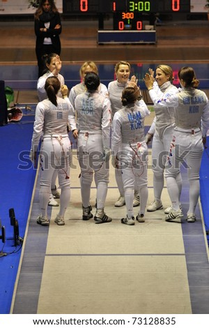 TURIN, ITALY - MARCH 13: Poland and Korea team congratulate each other before team tournament semifinal match of the 2011 Women world fencing cup on March 13, 2011 in Turin, Italy - stock photo