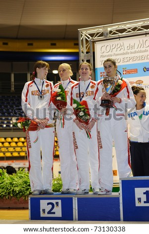 TURIN, ITALY - MARCH 13: Poland team (GRUCHALA RYBICKA SYNORADZKA WOJTKOWIAK) stands at first podium of team tournament of the 2011 Women world fencing cup on March 13, 2011 in Turin, Italy - stock photo