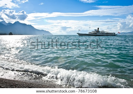 turist boat cruising on the lake on sunny day with shore in foreground, lake geneva, swiss