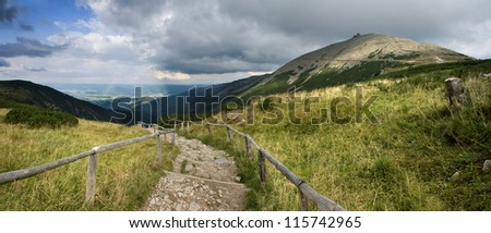 Turistic trail, mountains and rainbow. - stock photo
