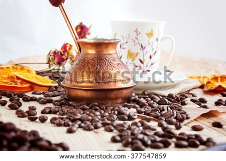 Turk and grain of coffee on a wooden table