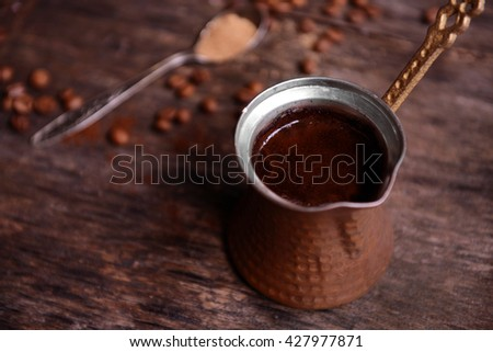 Turk of coffee with beans on wooden table