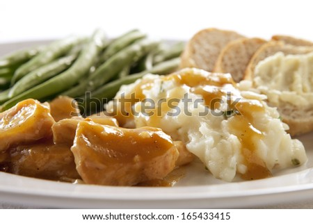 Turkey and Gravy Dinner with Mashed Potatoes, Green Beans and Bread - stock photo