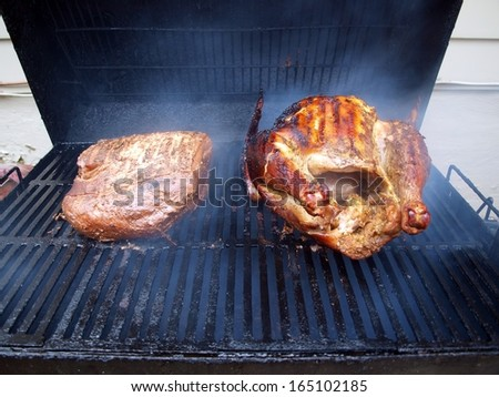 turkey and pork roast being smoked cooked on smoker grill - stock photo