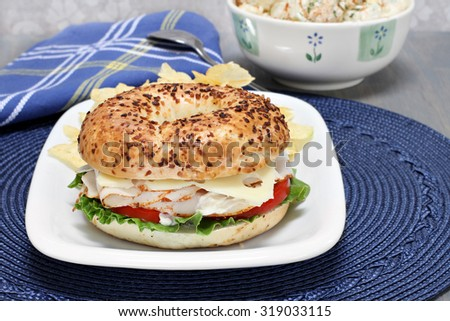Turkey breast, lettuce, tomato, and swiss cheese sandwich on an onion water bagel with a side of chips and potato salad.
