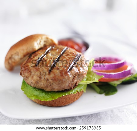 turkey burger on bun with lettuce and fixings atop while plate - stock photo