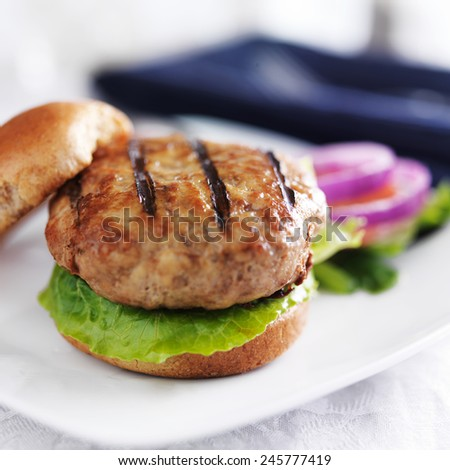 turkey burger on bun with lettuce and fixings close up - stock photo