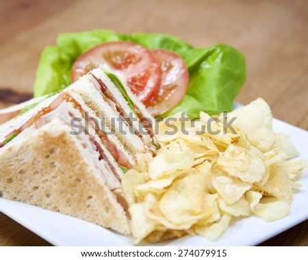 Turkey club sandwich and chips on a wooden table - stock photo