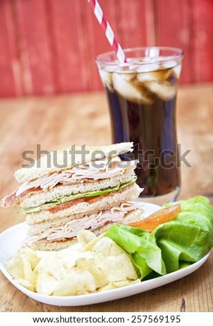 Turkey Club Sandwich with chips and soda - stock photo