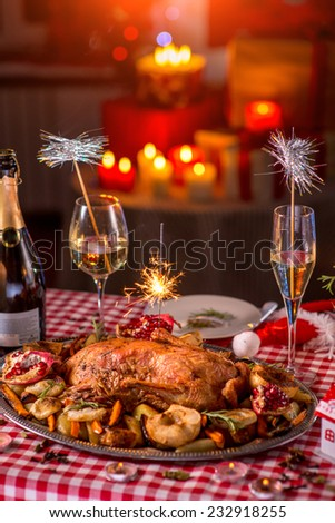 Turkey garnished with potato, apples, garnet and Bengal light on Christmas decorated table - stock photo