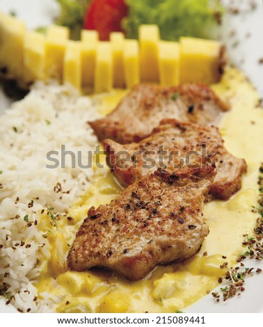 Turkey hen filet garnished with rice, pineapple and curry sauce - stock photo