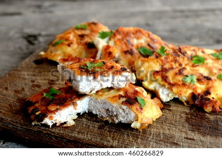 Turkey meat pieces fried in batter and garnished with parsley leaves. Cut Turkey cutlets on a cutting board and an old wooden background. Delicious poultry recipe  - stock photo