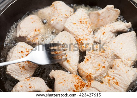 Turkey meat roasting on sunflower oil. Concept of unhealthy spicy food - stock photo