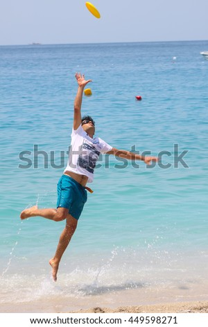 TURKEY - MUGLA; June 26, 2016, Attractive man playing frisbee on beach in summer sport fitness jump