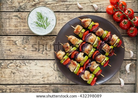 Turkey or chicken meat shish kebab skewers with tzatziki sauce, garlic and tomatoes on rustic wooden table background. Traditional barbecue grill food - stock photo