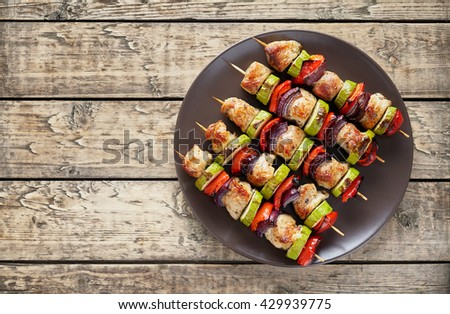 Turkey or chicken shish kebab skewers with pepper tomatoes and onion on rustic wooden table background - stock photo