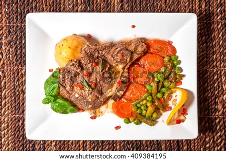 Turkey oven tray steak with fresh vegetables on a white plate and on a brown wattle place mat. Garnish of potatoes, carrots, green peas, with lemon and sweet basil decorations. - stock photo