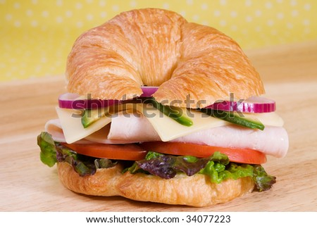 Turkey sandwich on a croissant with swiss cheese, avocado, tomatoes, lettuce, and onion.