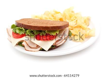 Turkey sandwich on rye bread with potato chips - stock photo