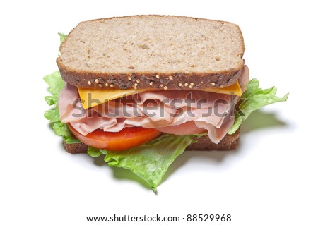 Turkey sandwich with lettuce, tomato and cheese on whole grain wheat bread isolated on a white background - stock photo