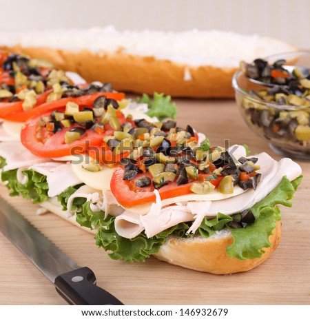 Turkey sandwich with lettuce, tomato and olives on french bread