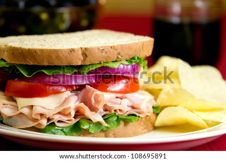 Turkey sandwich with swiss cheese, lettuce, tomato and onions.