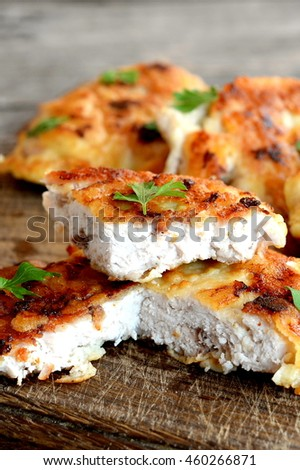 Turkey steaks fried in egg batter and garnished with fresh herbs. Appetizing fried meat slices on a cutting board and an old wooden background. Closeup  - stock photo