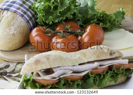 Turkey sub on rustic bread with tomato, bread, lettuce and cheese in the background with the sandwich in the foreground out of focus - stock photo